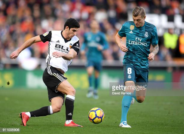 Goncalo Guedes of Valencia and Toni Kroos of Real Madrid battle for the ball during the La Liga match between Valencia and Real Madrid at Estadio...
