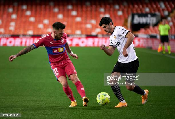 Goncalo Guedes of Valencia CF crosses under pressure from Josan Ferrandez of Elche CF during the La Liga Santander match between Valencia CF and...