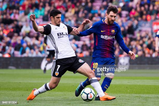 Goncalo Guedes of Valencia CF tackles Lionel Messi of FC Barcelona during the La Liga match between Barcelona and Valencia at Camp Nou on April 14...