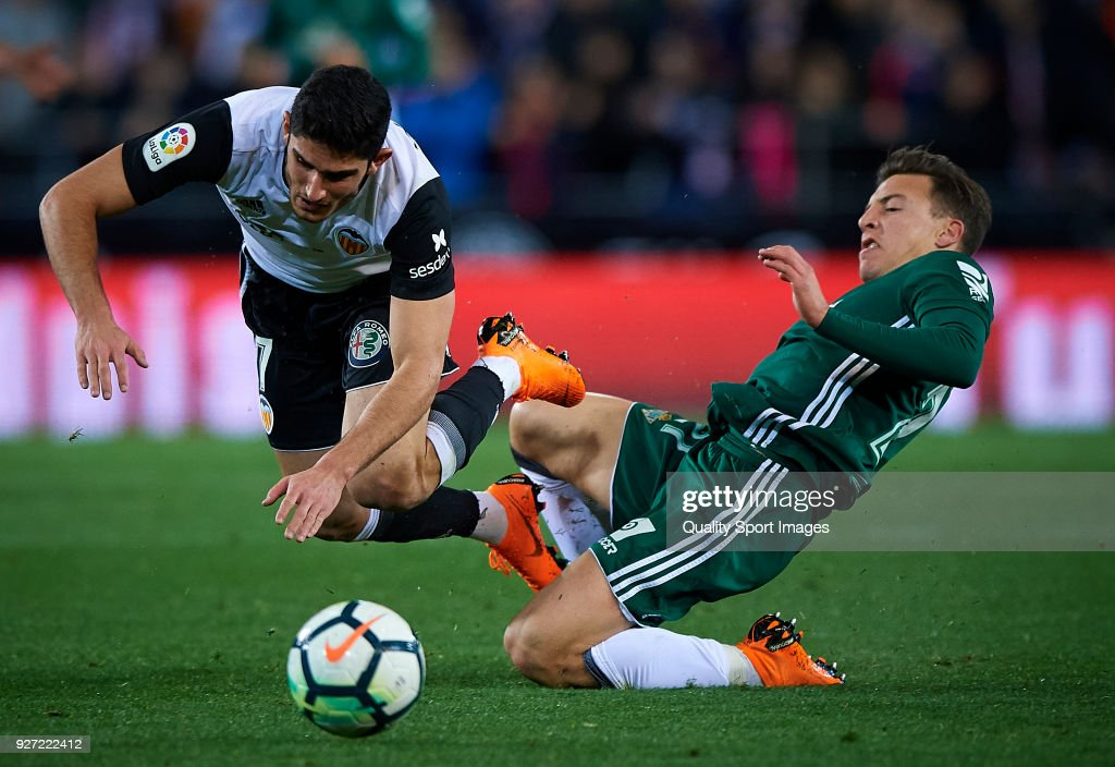 Goncalo Guedes (L) of Valencia competes for the ball with Francis of Real Betis during the La Liga match between Valencia and Real Betis at Mestalla Stadium on March 4, 2018 in Valencia, Spain.