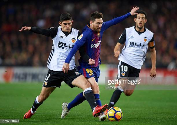 Goncalo Guedes of Valencia competes for the ball with Lionel Messi of Barcelona during the La Liga match between Valencia and Barcelona at Estadio...