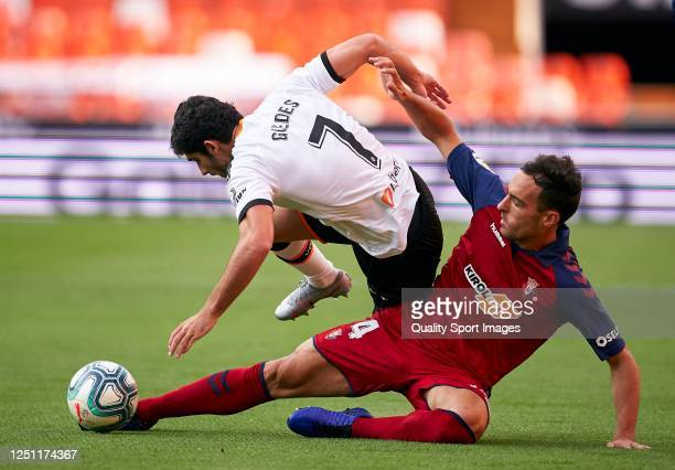 Goncalo Guedes of Valencia is tackled by Unai Garcia of Osasuna during the Liga match between Valencia CF and CA Osasuna at Estadio Mestalla on June...