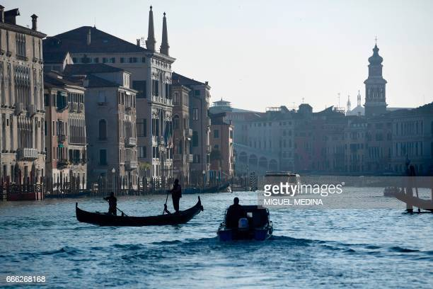 A gondola and a boat navigate on the Canale Grande in Venice on April 8 2017 / AFP PHOTO / MIGUEL MEDINA