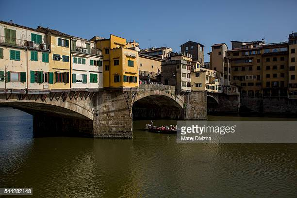A gondola crosses the Arno river under the Ponte Vecchio bridge on June 23 2016 in Florence Italy Florence is among Italy's most popular tourist...