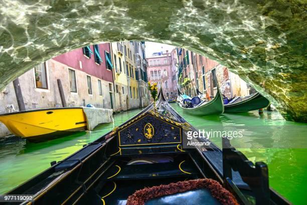 Gondola floating along canal under bridge, Venice, Italy