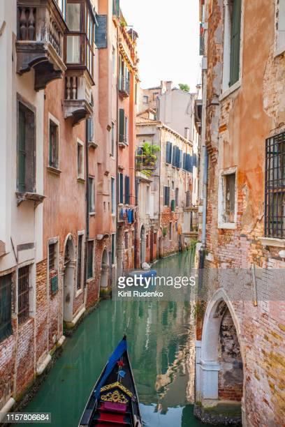 gondola on a canal in venice - luogo d'interesse internazionale foto e immagini stock