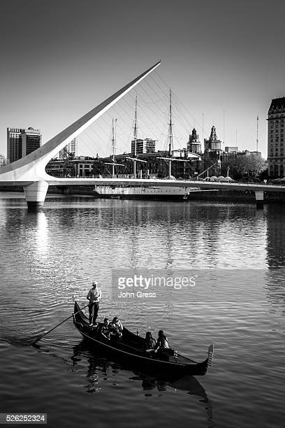 A gondola passes the Puente da la Mujer and the Museo Fragata Sarmiento is seen at sunset in the Puerto Madero neighborhood in Buenos Aires Argentina...