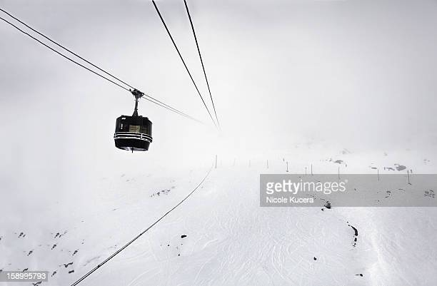 Gondola ride through clouds white out day in Alps