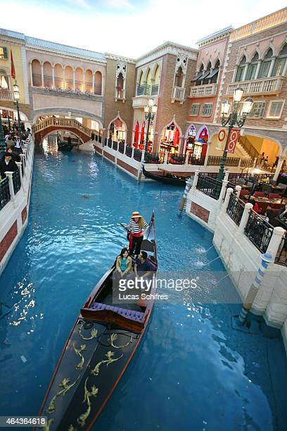 A gondola sails on a fake canal under a fake sky at the Venetian casino's shopping mall on February 24 2008 in Macau China The Venetian...