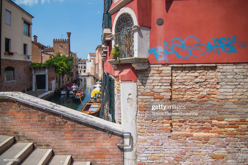 A gondola sails the canal of Avogaria, where there is a tag on the wall close to a votive shrine, through Dorsoduro district, on July 12, 2018 in Venice, Italy. The plague of graffiti and tags on the walls of the palaces of Venice continues with new writing across the doors, windows and the plaster of shops, banks, historic buildings, ruining and attacking the priceless architectural heritage of the lagoon. Venice has been living with this problem for years, but it has not reached a resolution until today.