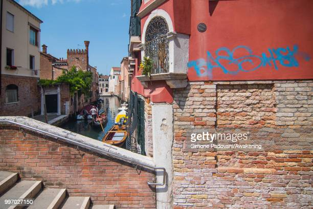 A gondola sails the canal of Avogaria where there is a tag on the wall close to a votive shrine through Dorsoduro district on July 12 2018 in Venice...