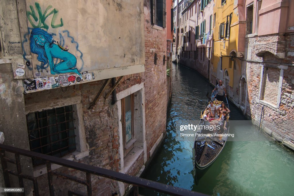 A gondola sails under the bridge of Salizada San Giovanni Grisostomo where there is a graffiti on the wall representing a blue naked woman with a gondola on her back, on the way that connects railway station S. Lucia to Rialto bridge, through Cannaregio district, on July 12, 2018 in Venice, Italy. The plague of graffiti and tags on the walls of the palaces of Venice continues with new writing across the doors, windows and the plaster of shops, banks, historic buildings, ruining and attacking the priceless architectural heritage of the lagoon. Venice has been living with this problem for years, but it has not reached a resolution until today.