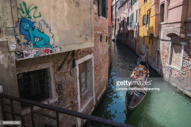 A gondola sails under the bridge of Salizada San Giovanni Grisostomo where there is a graffiti on the wall representing a blue naked woman with a...