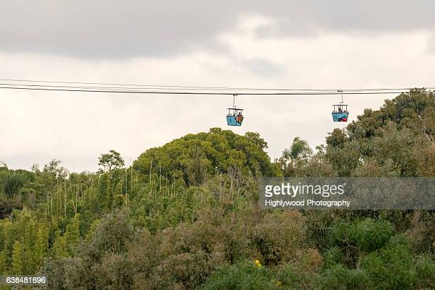 gondola stretches across the san diego sky with storm clouds behind them - highlywood stock pictures, royalty-free photos & images