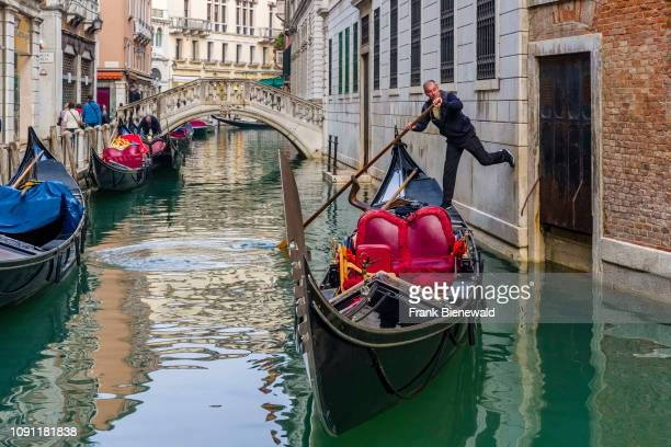 Gondola, the traditional venetian rowing boat, is cruising on a small canal between the ailing brick houses of the so-called 'Floating city'.