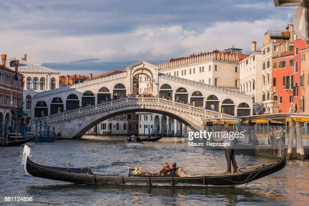 Gondola tour with tourist in front of Rialto Bridge at Venice, Italy.