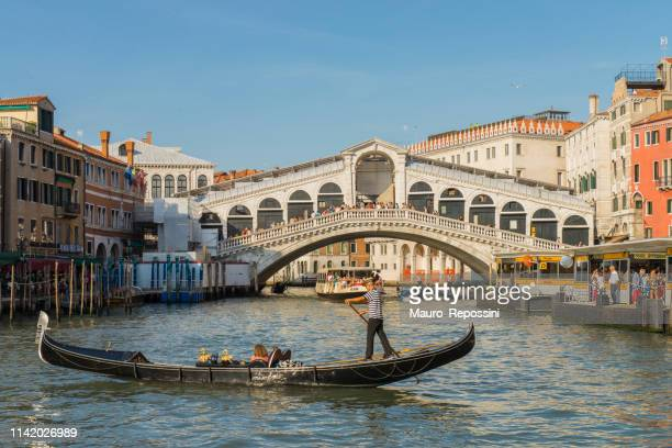 gondola tour with tourist near the rialto bridge at venice, italy. - gondola traditional boat stock pictures, royalty-free photos & images