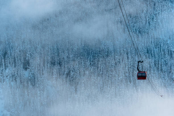 Gondola traverses valley in fresh snow and clouds