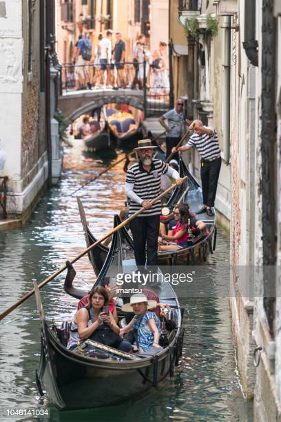 gondola with gondolier and tourists - gondola traditional boat stock pictures, royalty-free photos & images