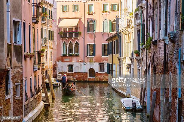 Gondola with tourists on a canal in the old town of Venice, Italy