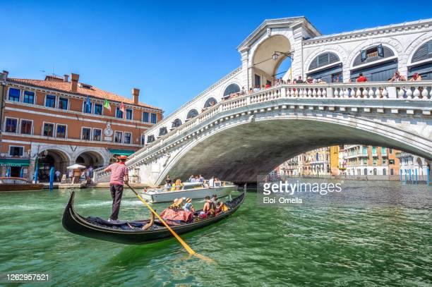 góndola con turistas en gran canal con puente de rialto, venecia - venecia fotografías e imágenes de stock