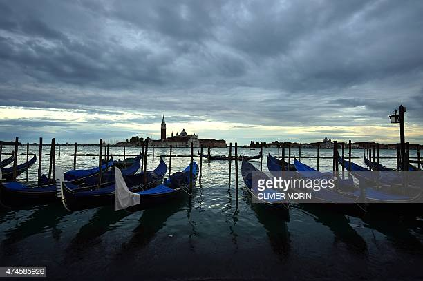 Gondolas are pictured at sunset in front of St Mark's square in the city of Venice on May 23 2015 AFP PHOTO / OLIVIER MORIN