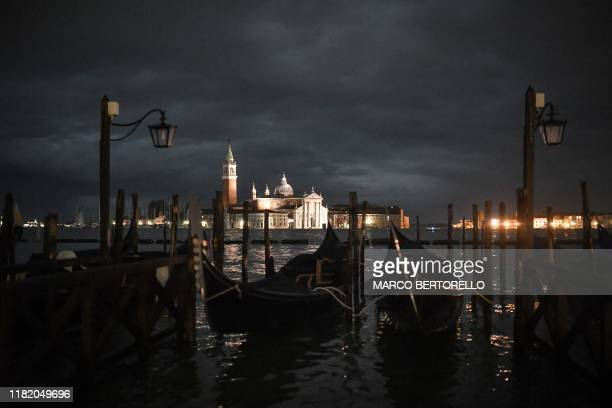 """Gondolas are pictured by the Venetian lagoon during an exceptional """"Alta Acqua"""" high tide water level on November 12, 2019 in Venice. - Powerful..."""