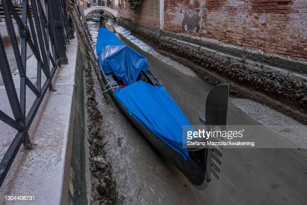 February 27: Gondolas are stucked in low tide in a little canal on February 27, 2021 in Venice, Italy. An exceptional low tide affected Venice this...