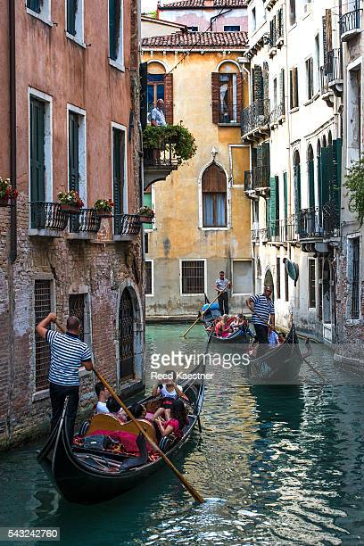 Gondolas carry tourists on the canals of Venice Italy