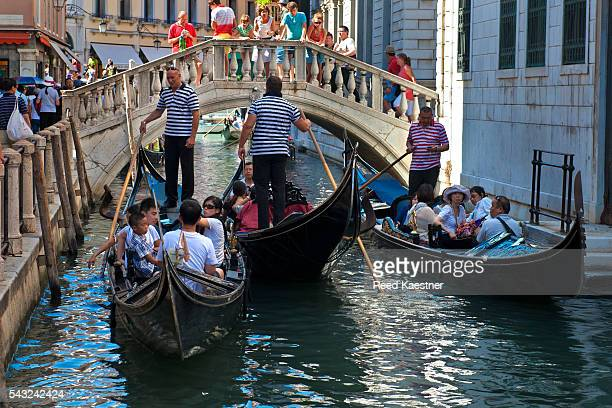 Gondolas carry tourists on the canals of Venice Italy. Some water ways get crowded in the summer.