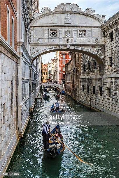 Gondolas carry tourists under the Bridge of Sighs in Venice Italy
