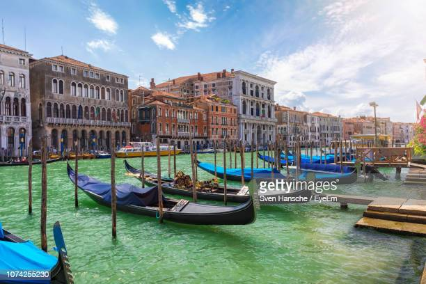 gondolas moored on canal against buildings in city - ヴェネツィア ストックフォトと画像