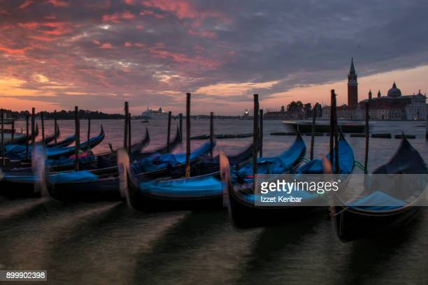Gondolas swaying with waves, at San Marco, during early morning , Venice, Italy