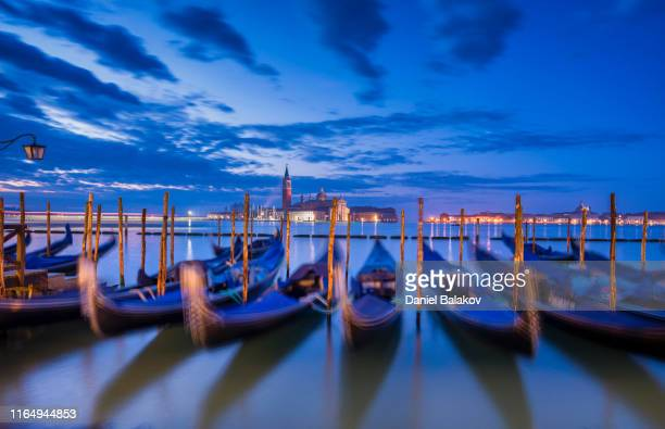 pov. gondolas. vacations in venice, italy-city of romance. typical venetian sights with the city lights under the night sky. - gondola traditional boat stock pictures, royalty-free photos & images