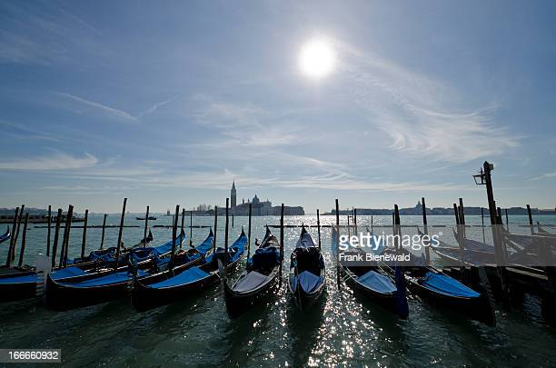 Gondolas waiting for tourists at the pier in front of San Marco Square San Giorgio Maggiore in the back