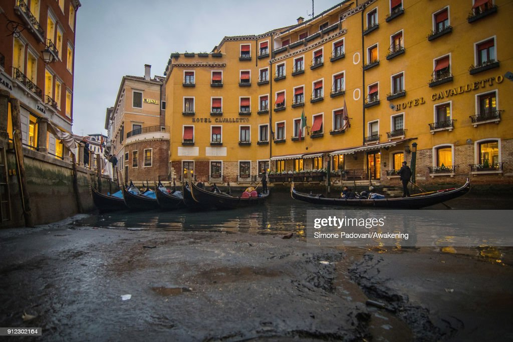 Gondolers sail on one side of the Bacino Orseolo, near St. Mark square, because of an exceptional low tide on January 30, 2018 in Venice, Italy. An exceptional low tide affected Venice this afternoon creating problems in transport and navigation.