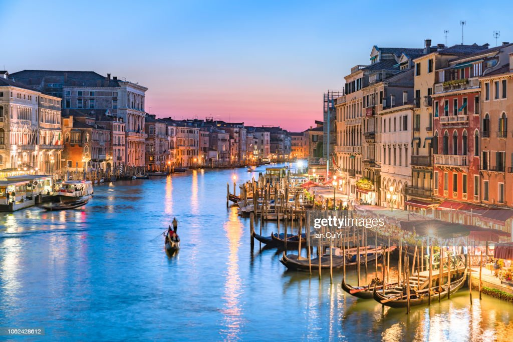Gondolier Heads into the Sunset Along Venice's Grand Canal (Sunset) : Stock Photo
