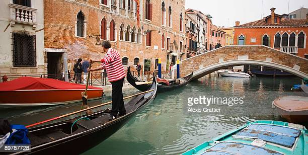 Gondolier in canal, Venice, Italy