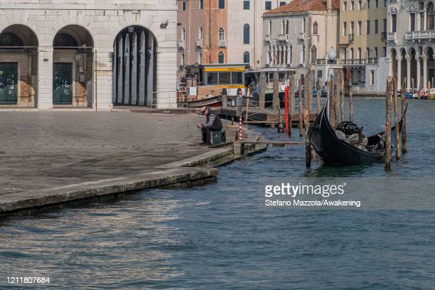 A gondolier looks at his cell phone on March 11 2020 A local walks near the Grand Canal with a protective face mask in Venice Italy The Italian...