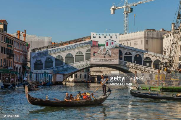 A gondolier navigating tourist on a gondola in the Grand Canal is seen in the foreground of the famous Rialto Bridge going under restoration on July...