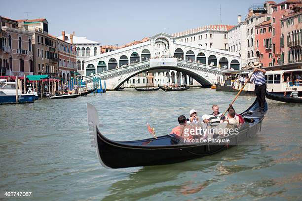 CONTENT] Gondolier riding gondola on Grand Canal and showing Venice to a group of tourists Rialto Bridge and some buildings on background July 15 2013