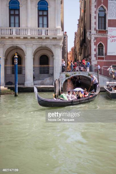 Gondolier riding gondola on Grand Canal and showing Venice to a group of tourists. A bridge and some Italian buildings on background. July 15, 2013.