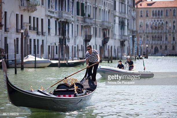 CONTENT] Gondolier riding gondola on Grand Canal of Venice Speedboat with some Italian policemen on background