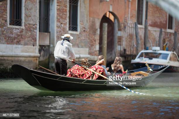 CONTENT] Gondolier riding gondola on narrow canal and showing Venice to a group of tourists Some apartment buildings on sides