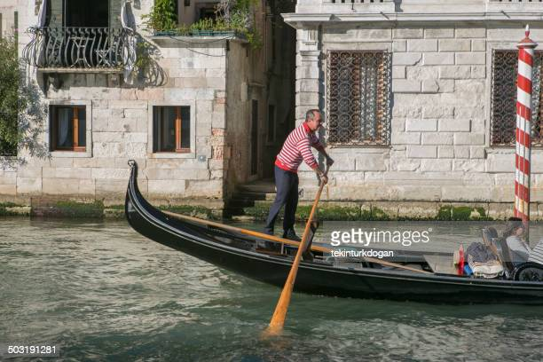 gondolier riding traditional gondola at grand canal of venice italy - gondola traditional boat stock pictures, royalty-free photos & images