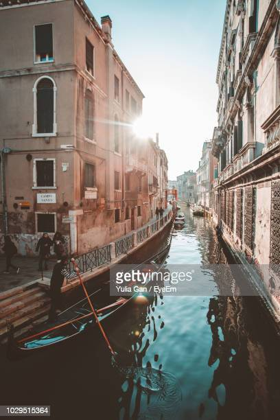 gondolier rowing on gondola - traditional boat in canal against sky - gondola traditional boat stock pictures, royalty-free photos & images