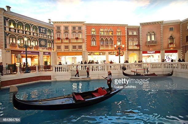 A gondolier sails on a fake canal under a fake sky at the Venetian casino's shopping mall on February 24 2008 in Macau China The Venetian...