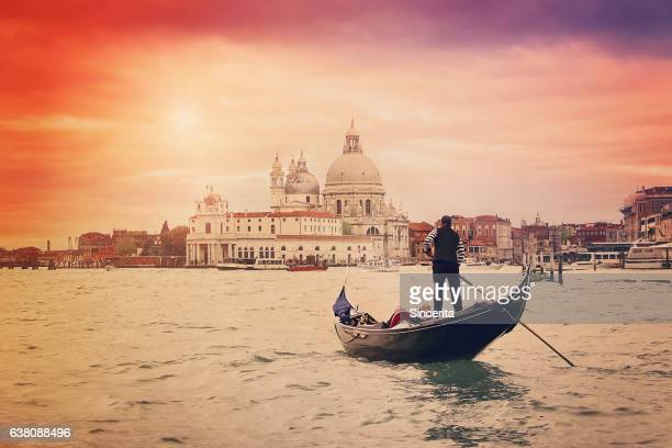 gondolier with tourists on the grand canal and santa maria della salute , venice, italy - gran canal venecia fotografías e imágenes de stock