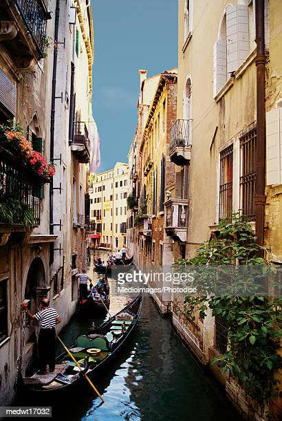 gondoliers and gondolas on canal in venice, italy - travel14 stock pictures, royalty-free photos & images