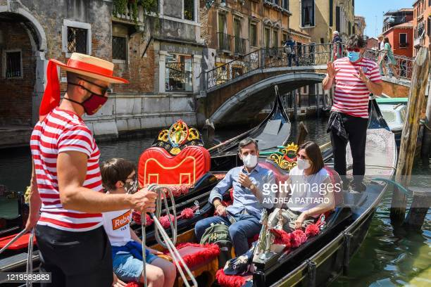 Gondoliers go with customers for a gondola ride on a canal in Venice on June 12, 2020 as the country eases its lockdown aimed at curbing the spread...